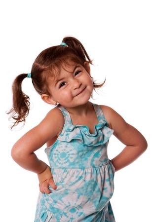 態度作り笑いとかわいい小さな若い幼児女の子手を腰と分離した髪におさげ髪。