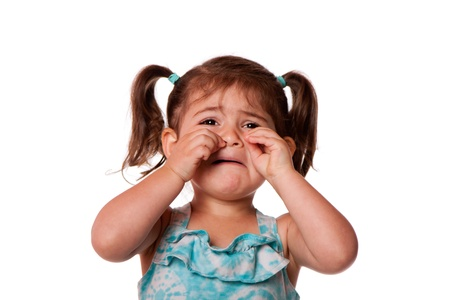 child crying: Sad unhappy crying cute little young toddler girl wiping tears, isolated. Stock Photo