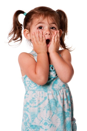 Cute adorable toddler girl surprised innocent expression with hands on cheeks, isolated. Archivio Fotografico