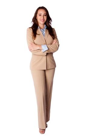 administracion de empresas: Hermoso atractivo feliz sonriente mujer de negocios corporativos de pie con los brazos cruzados en traje beige, aislado.