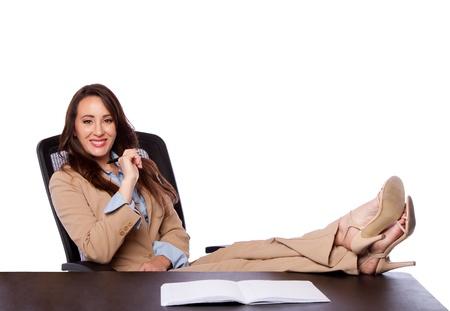 pies bonitos: Hermoso atractivo feliz mujer de negocios corporativos abogado sentado en la oficina de la pluma explotaci�n y los pies sobre el escritorio, aislado. Foto de archivo