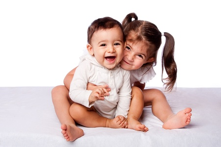 innocense: Cute lovely toddler sister hugging happy baby brother while sitting, family concept, on white.