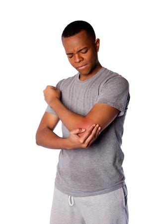 codo: Hombre deportivo con una lesión en el codo doloroso deportes en camisa gris y pantalones deportivos, aislado.
