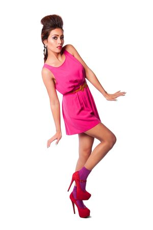 body curve: Beautiful attractive fashion woman in pink dress showing curves, long legs, and funky hairstyle.