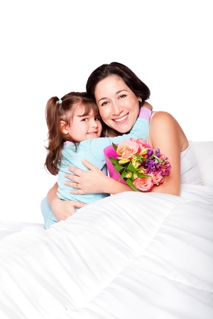 Cute child giving flowers and hug to mom in bed, mother day or hospital concept, isolated.