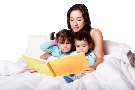 Mother reading bed time story book to daughter and son kids in bed, isolated. photo
