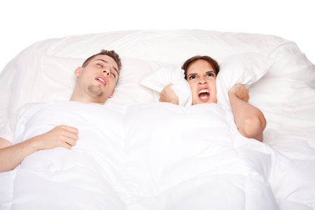 Couple laying asleep in bed while man snores and woman holds pillow over ears. Stock Photo