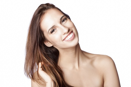 haircare: Beautiful happy smiling woman showing teeth with great skin touching her hair, skincare and haircare concept, isolated.