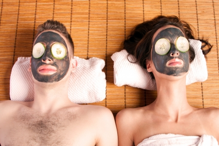 facial: Couples holiday retreat at spa getting facial mask with cucumber skincare relaxing beauty treatment on bamboo.