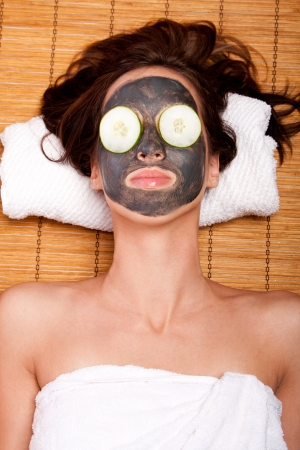 resting mask: Woman face with beauty treatment skincare mask and cucumber laying on bamboo at spa.