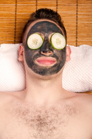 Man face with beauty treatment skincare mask and cucumber laying on bamboo at spa. 免版税图像