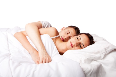 happily: Young couple happily sleeping in white bed, isolated. Stock Photo