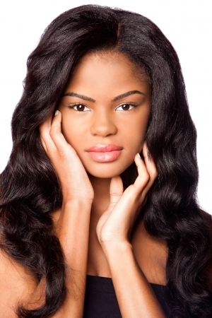 Beautiful African-American young woman with clean skin and hands in face and big wig hair extensions, makeup cosmetics haircare concept, on white.