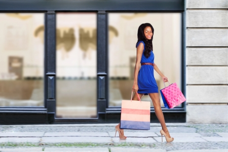 street fashion: Beautiful young fashion woman with shopping bags walking in street passing store.