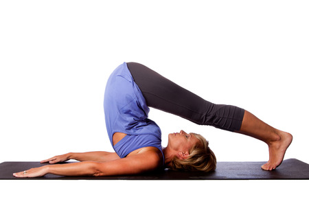 plows: Back stretch Plow Halasana yoga pose by beautiful healthy woman with legs over her head, on white. Stock Photo
