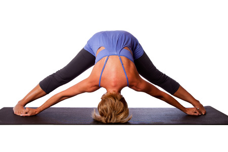 inversion: Beautiful healthy woman doing inversion Standing Intense Spread Leg Prasarita Padottanasana yoga pose with head on floor, on white. Stock Photo