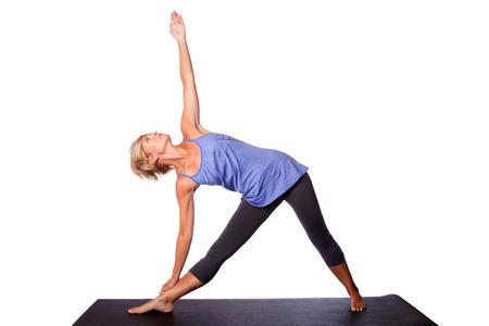 trikonasana: Beautiful healthy woman doing Triangle Utthita Trikonasana yoga pose standing on mat, on white. Stock Photo