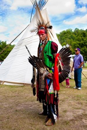 guerriero indiano: Whitesburg, GA - 29 settembre: guerriero indiano nativo americano con le armi in piedi davanti Tipi al McIntosh Fall Festival, 29 settembre, 2013 in Whitesburg, GA. Editoriali