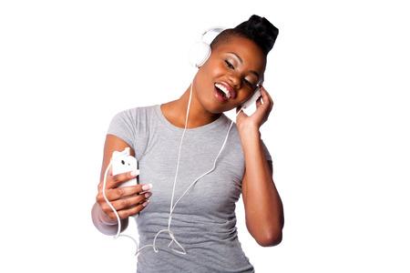 cantando: Mujer joven hermosa con los auriculares y el dispositivo m�vil escuchando ranurado canto a la m�sica, aislado en blanco.