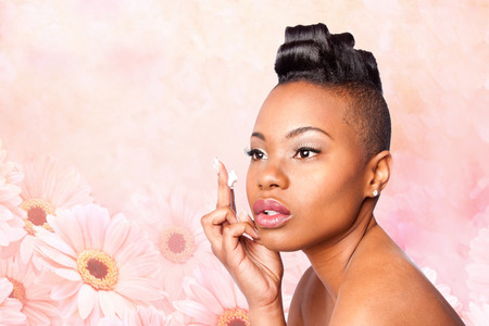 aging face: Face of beautiful woman applying facial moisturizer exfoliating anti wrinkle aging cream under eyes, skincare concept, on pink flowers.