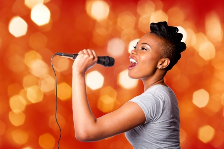 Beautiful teenager woman singing kareoke concert artist holding microphone, on red orange blurred lights background. Archivio Fotografico