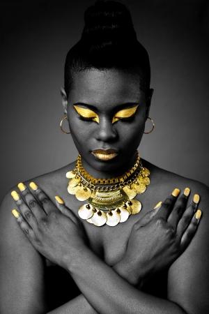 ゴールドのアイシャドウと腕を組んで暗いとダウン見ているネックレスの美しいアフリカ部族ファッション。