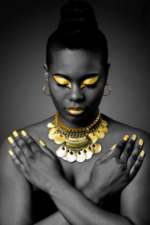 Beautiful African tribal fashion with gold eyeshadow and necklace on dark with arms crossed and looking down. Archivio Fotografico
