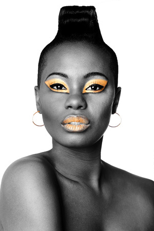 gold facial: Beautiful face of black African fashion woman with gold makeup cosmetics on white. Stock Photo