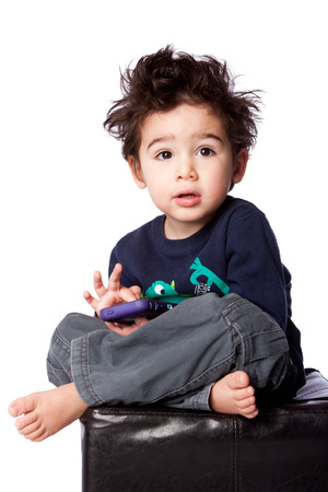 Cute toddler boy sitting with mobile device and crazy hair, isolated. photo