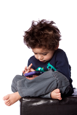 Cute toddler boy sitting playing games on mobile device and crazy hair, isolated. photo