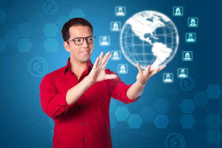 male and female: Business man in red shirt using futuristic global network marketing interface of hologram Earth with male female icons on blue.