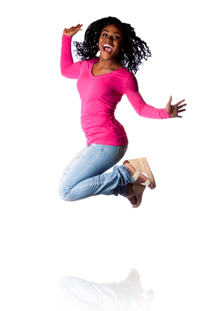 Beautiful young woman jumping of happiness celebrating and cheering, wearing blue jeans and pink shirt.