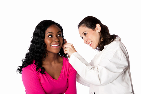 otoscope: Happy smiling doctor physician checking patient ear for infection with otoscope, isolated. Stock Photo