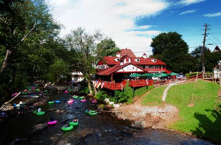 Helen, GA, USA - Aug. 31 2014: Tourists having fun tubing in Chattahoochee river passing restaurant cafe in Alpine Helen, GA.