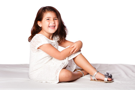 beautiful cute happy smiling girl sitting, on white. photo