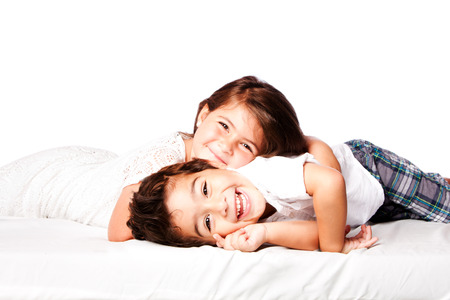 kids hugging: Happy smiling siblings brother sister together laying. Stock Photo
