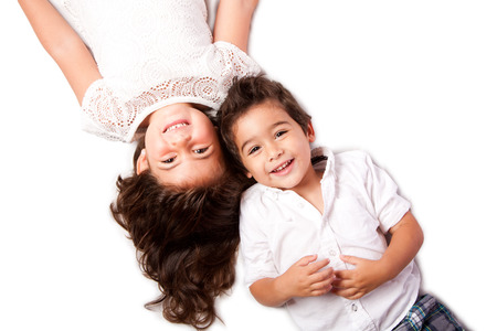 Beautiful happy smiling cute family siblings brother sister laying together on white. photo