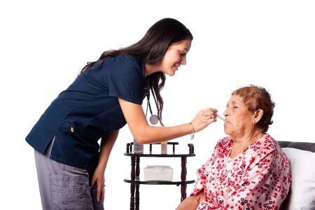 elderly people: Nurse measuring temperature of senior woman, healthcare home health concept.
