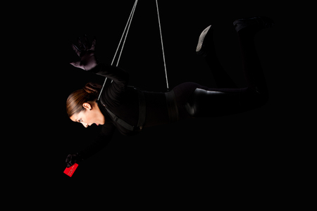 identity theft: Beautiful woman hanging from wire cables stealing credit card, identity theft crime concept. Stock Photo
