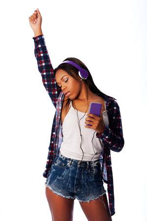 Beautiful teenager girl listening, dancing and jamming to music on mobile phone wearing purple headphones, on white. Stock Photo