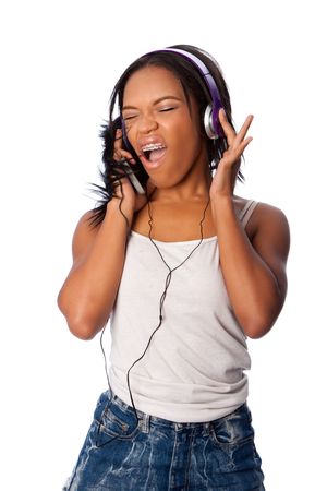 Beautiful teenager happily singing along jamming while listening to music, on white.