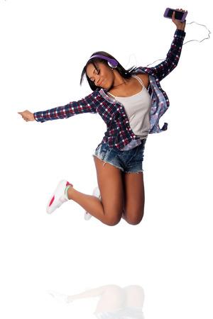 Beautiful happy teenager jumping dancing jamming listening to music, on white. Imagens