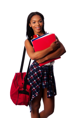 Beautiful happy student standing with binders, books, notepads and bag, on white.