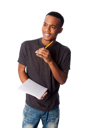 Handsome happy student standing thinking with pencil and notepad coming up with ideas, on white. Imagens