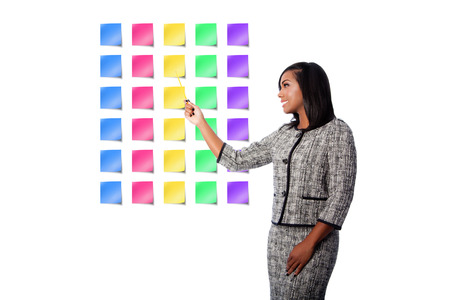 Beautiful happy smiling business woman presenting colorful blank sticky notes, on white. Imagens