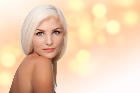 mujer rubia desnuda: Hermoso rostro de mujer joven de Estética concepto de cuidado de la piel facial mirando por encima del hombro, sobre fondo luces borrosa. Foto de archivo