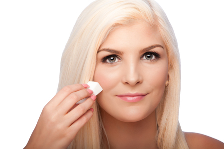 Beautiful face of young woman for Aesthetics facial skincare concept wiping applying makeup cosmetics, on white. Imagens
