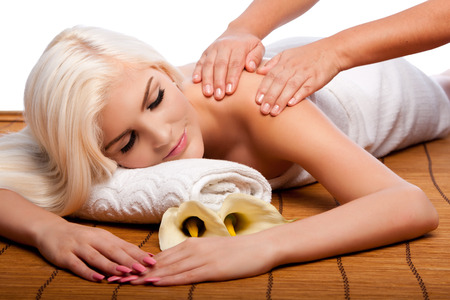 Beautiful young woman relaxing at spa getting therapeutic pampering shoulder massage.