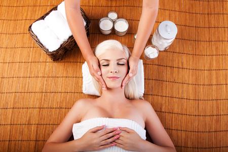 mimos: Hermosa mujer de relax en el balneario que consigue masaje facial terapéutico mimos, que pone en bambú. Foto de archivo