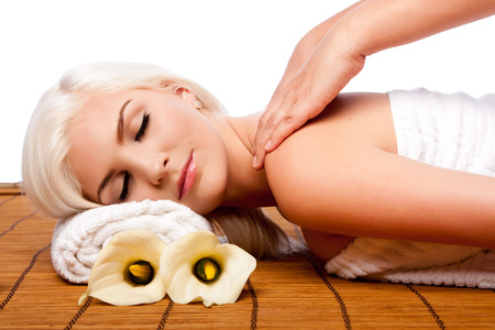 mimos: Beautiful young woman relaxing at spa getting therapeutic pampering shoulder massage.